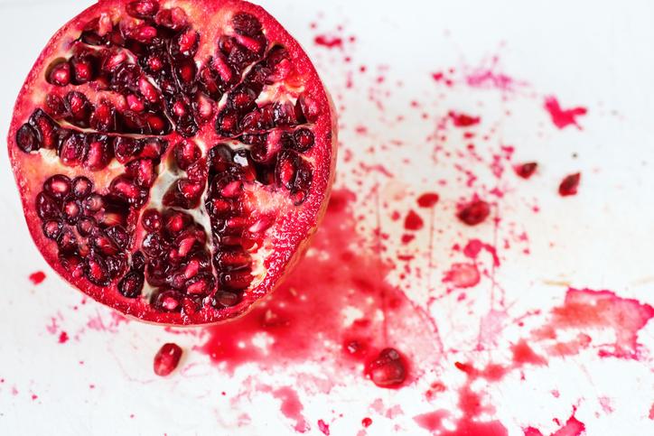 Sliced pomegranate with splashing background
